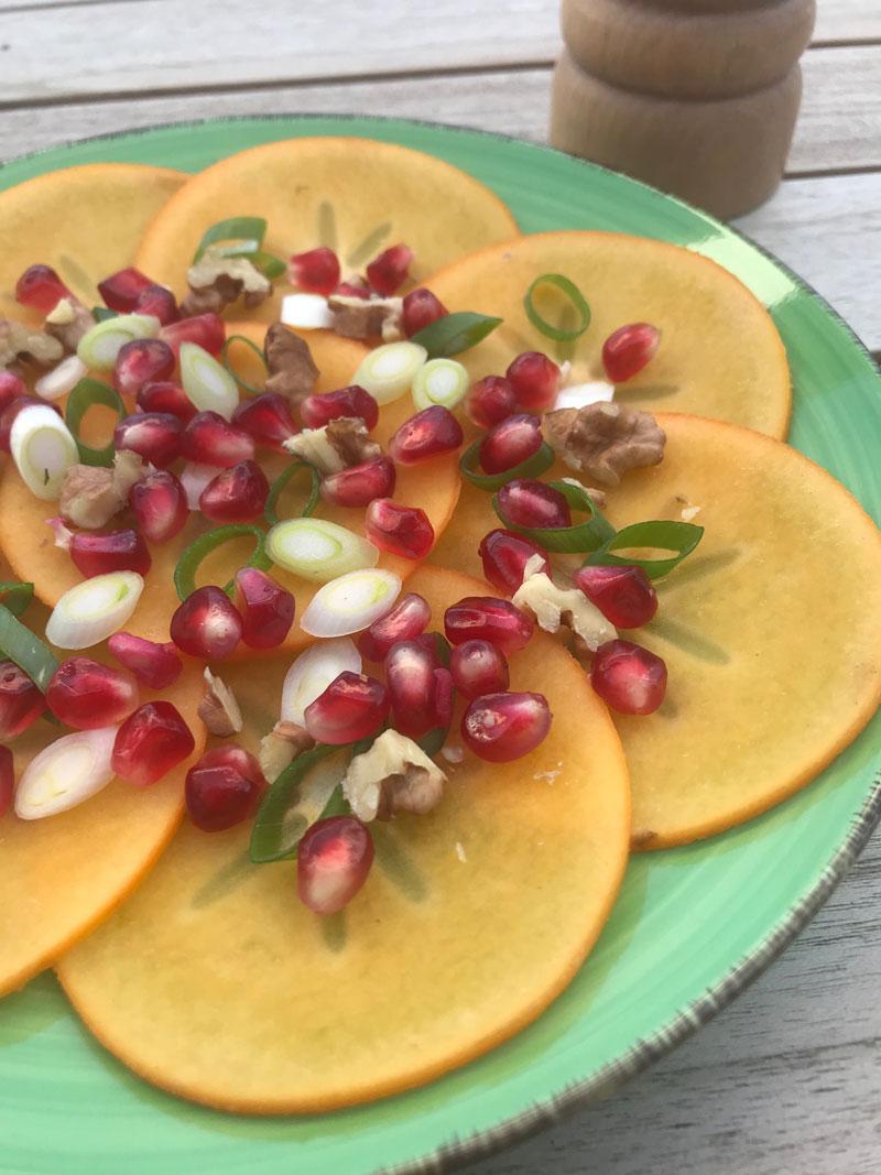 Kaki carpaccio with pomegranate shallots and walnus